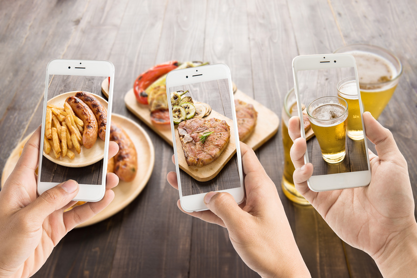 friends using smartphones to take photos of sausage and pork chop and beer.